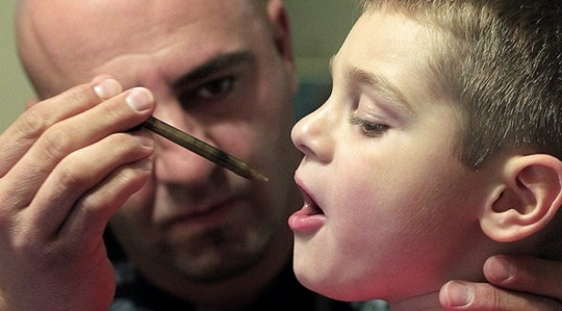 Child being treated with CBD oil drop