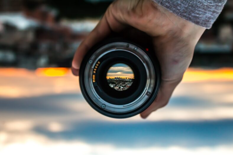 strains for focus header: camera lens in front of sunset.